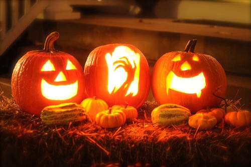 Three well lit Jack-o'-lanterns showing differently carved designs