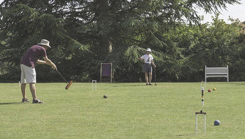 Two people playing croquet in the park
