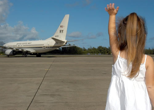 Girl waving goodbye to an airplane