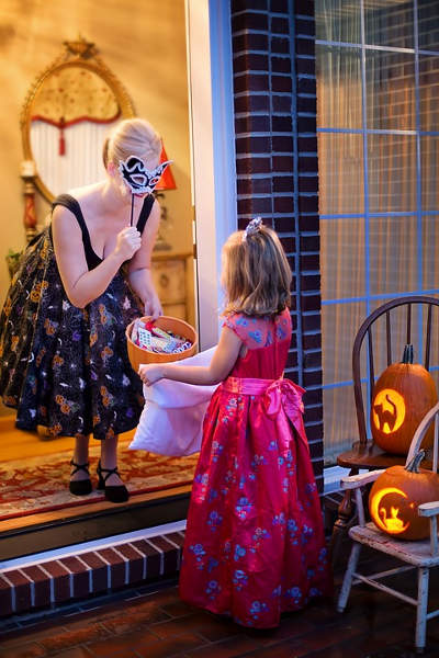 A girl receiving treats from a lady on Halloween