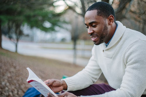 A man reading a book in the park