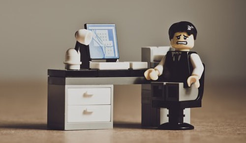 A writer sitting at computer and desk (Lego style)